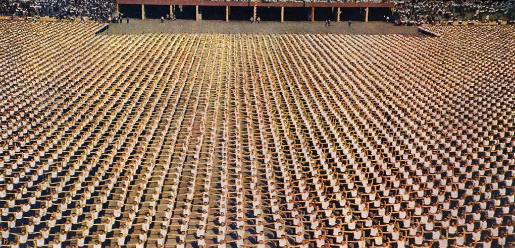 Men fill the stadium field performing calisthenics (photo by Karel Šmirous)